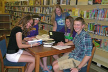 A group of teens studying at the library.
